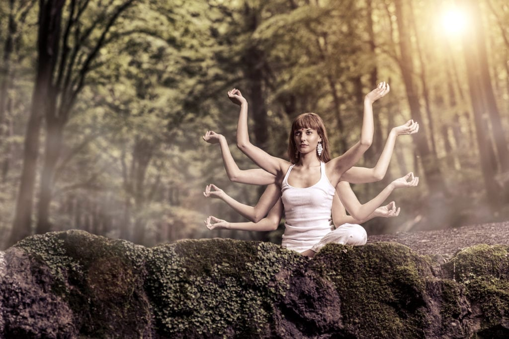 A young woman meditates in a forest, the sun filters through the trees. Her eight arms are in a pose like goddess Kali.